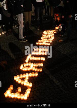 """Berlin, Allemagne. Mar 25, 2017. Les bénévoles de la World Wildlife Fund (WWF) place des bougies pour former les mots """"Earth Hour"""" pour l'assemblée annuelle de l'événement Heure de la Terre à Berlin, capitale de l'Allemagne, le 25 mars 2017. Credit: Shan Yuqi/Xinhua/Alamy Live News Banque D'Images"""