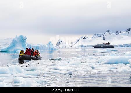 Les touristes de l'antarctique en zodiac parmi Antarctic iceberg. Banque D'Images