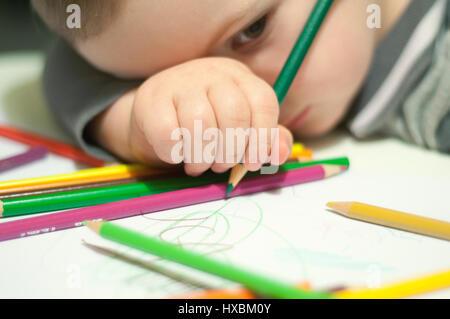Enfant s'appuie sur un livre blanc à l'aide de crayons Banque D'Images