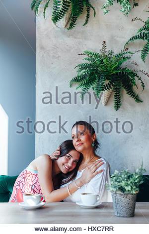 Mère et fille embrassant dans un café Banque D'Images