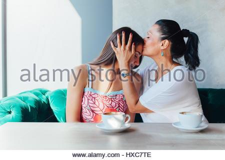Mère embrassant sa fille dans un café Banque D'Images