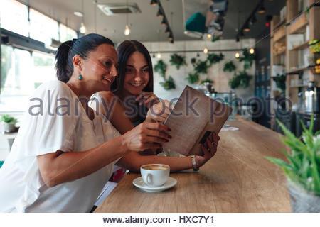 Mère et fille de boire du café et à la recherche au menu café Banque D'Images