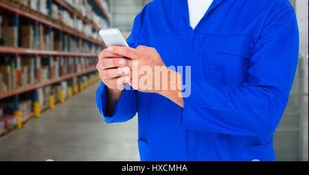 Digital composite de mécanicien holding up téléphone contre l'entrepôt floue Banque D'Images