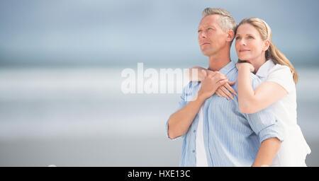 Digital composite of Woman with arms autour de l'homme contre la plage floue Banque D'Images