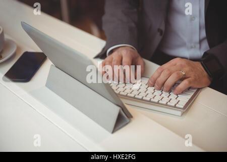 Portrait of businessman using digital tablet in coffee shop