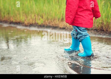 La marche de l'enfant dans la flaque en wellies sur temps de pluie Banque D'Images