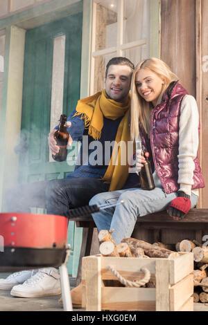 Happy young couple boire de la bière et à la recherche au grill on porch Banque D'Images