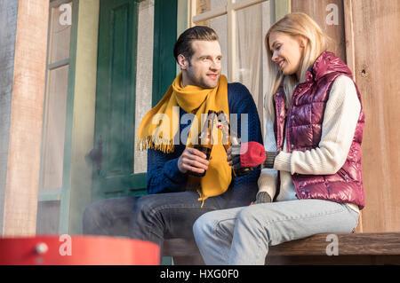 Happy young couple clinking beer bottles, assis sur banc en bois Banque D'Images
