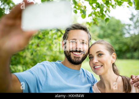 Couple heureux en amour en tenant avec smartphone selfies Banque D'Images