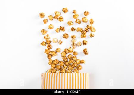 Vue de dessus du maïs soufflé au récipient blanc sur papier Banque D'Images