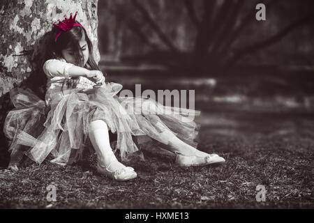 La princesse s'ennuie; petite fille triste et solitaire avec couronne rose Banque D'Images