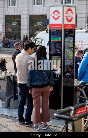 Deux touristes asiatiques en utilisant une machine pour louer un vélo à l'extérieur de la station de métro Green Banque D'Images