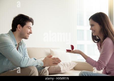 Jeune femme en donnant l'occasion de fiançailles, proposant petit ami de se marier Banque D'Images