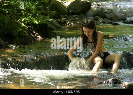 Jeune fille jouant dans l'eau de montagne froide dans une journée d'été Banque D'Images