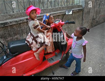 Zanzibar, Tanzanie - le 16 février 2008: Groupe de plusieurs petites filles africaines jouent près de scooter rouge Banque D'Images