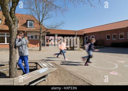 Les enfants à l'école primaire joue à cache-cache pendant les pauses