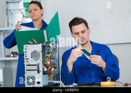 Équipe d'étudiants l'examen et la réparation de pièces d'ordinateur