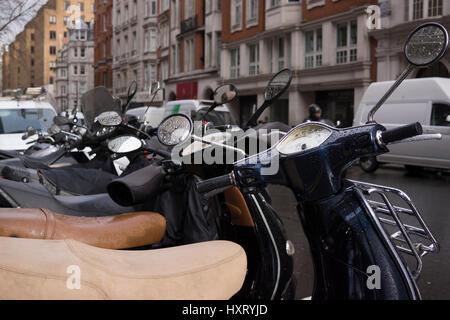 Une rangée de scooters Vespa garé dans une rue de Londres, Mayfair après la pluie. De nombreuses personnes se sont Banque D'Images