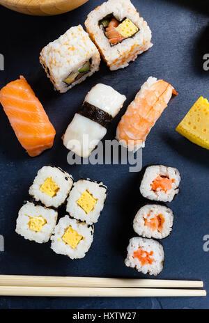 Bac en ardoise noire d'un assortiment de sushi et de rouleaux. Banque D'Images