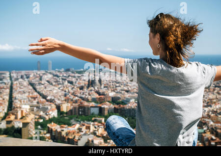 Jeune femme heureuse se cale à l'appareil photo avec les mains. Traveler appréciant les rues de la région de montagne, Banque D'Images