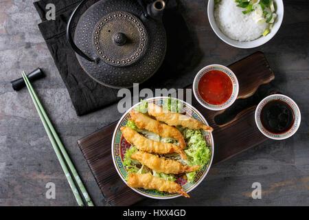 Poêlée de Crevettes tempura sur laitue salade avec des sauces. Servi dans la Chine traditionnelle avec des baguettes Banque D'Images