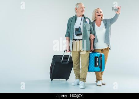 Happy senior couple avec des sacs de voyage sur smartphone selfies, concept de voyage Banque D'Images