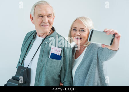 Portrait of smiling senior couple avec les passeports et les billets faisant voyager selfies sur smartphone, concept Banque D'Images