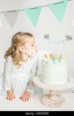 Belle petite fille dans diadem qui souffle sur le gâteau d'anniversaire Banque D'Images