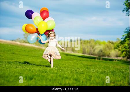 Petite blonde fille courir avec bouquet de ballons colorés dans la campagne Banque D'Images