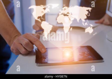 Global business concept avec une carte du monde avec au-dessus d'une tablette numérique et une équipe de deux hommes Banque D'Images