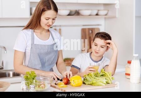 L'alimentation saine. Plaisir positif teanage girl couper des légumes et salade préparation tout en se tenant dans Banque D'Images