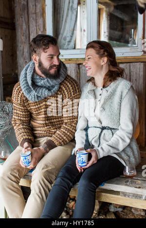 La Suède, jeune couple assis sur un banc et parler Banque D'Images