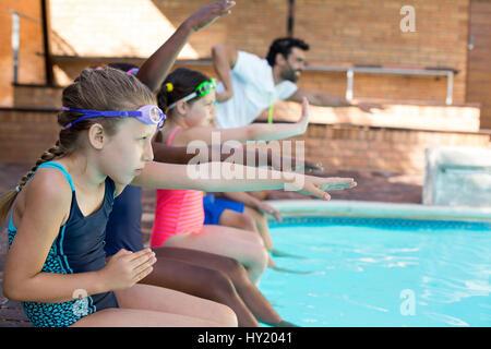 Moniteur de natation homme d'aider les jeunes filles au bord de la piscine Banque D'Images