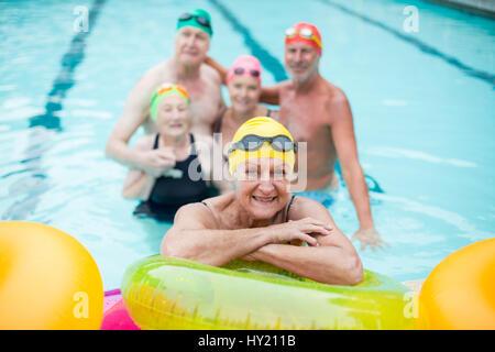 Portrait of senior woman par anneaux gonflables avec des amis en arrière-plan Banque D'Images