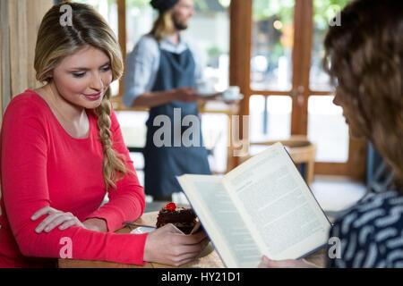 Jeune femme à l'aide de téléphone en ami reading book in coffee shop Banque D'Images