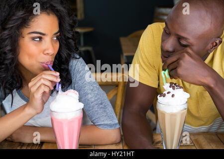Jeune couple aimant avoir des milkshakes à table in coffee shop Banque D'Images