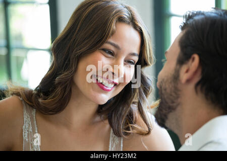 Smiling young woman looking at man in restaurant Banque D'Images