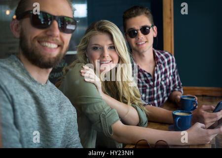 Portrait of happy amis masculins et féminins à table in cafe Banque D'Images