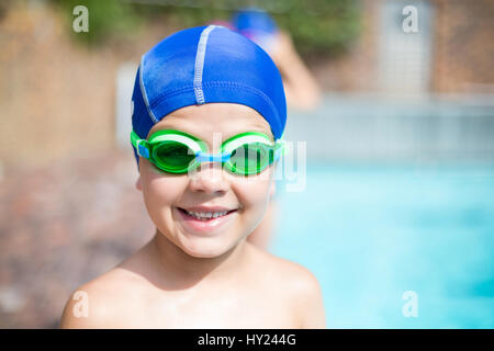 Close up portrait of little boy wearing swimming goggle et cap at poolside Banque D'Images