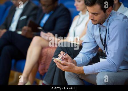 Direction d'entreprise participant à une réunion d'affaires prise de notes au centre de conférence Banque D'Images