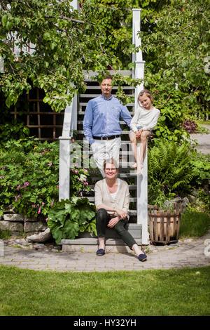 La Suède, vastmanland, vasteras, portrait de famille avec sa fille (8-9) in backyard Banque D'Images
