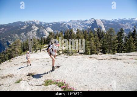 États-unis, Californie, Yosemite, Girl (12-13) and boy (14-15) à pied de la haute montagne avec vue sur le dôme Banque D'Images