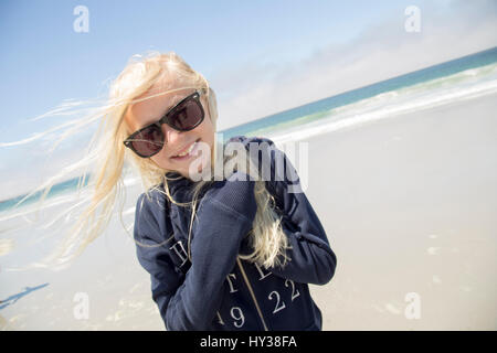 États-unis, Californie, carmel-by-the-Sea, smiling blonde girl (12-13) wearing sunglasses on beach Banque D'Images