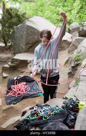 La Suède, Vastergotland, Boy (14-15) avec des cordes d'escalade dans les rochers