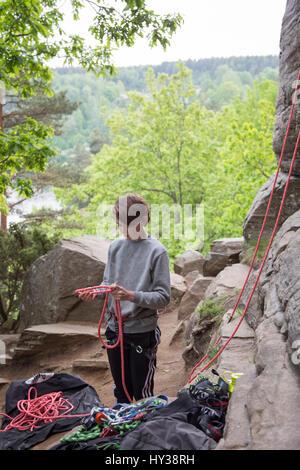 La Suède, Vastergotland, Boy (14-15) avec des cordes d'escalade en montagne
