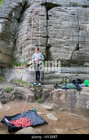 La Suède, Vastergotland, Boy (14-15) avec des cordes d'escalade au pied du rocher