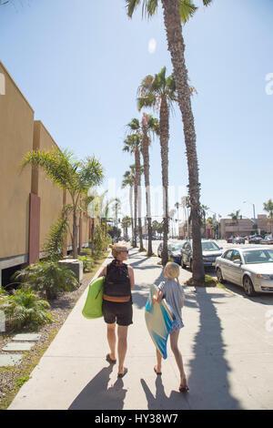 États-unis, Californie, San Diego, Femme et fille marchant sur un trottoir avec des palmiers le long de celle-ci Banque D'Images
