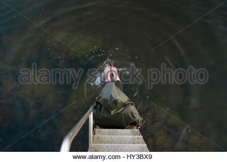 La Suède, vastra sweden huskvarna, overhead view of young woman sitting on steps dans le lac Banque D'Images