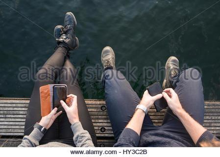La Suède, Stockholm, Malmö, overhead view of young man and woman sitting on pier avec les téléphones intelligents Banque D'Images