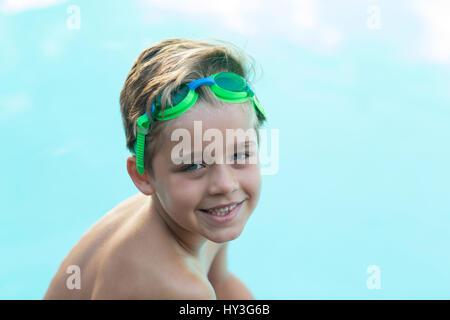 Portrait of smiling little boy wearing green lunettes de natation Banque D'Images